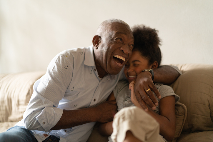 Grandfather laughing and hugging his granddaughter