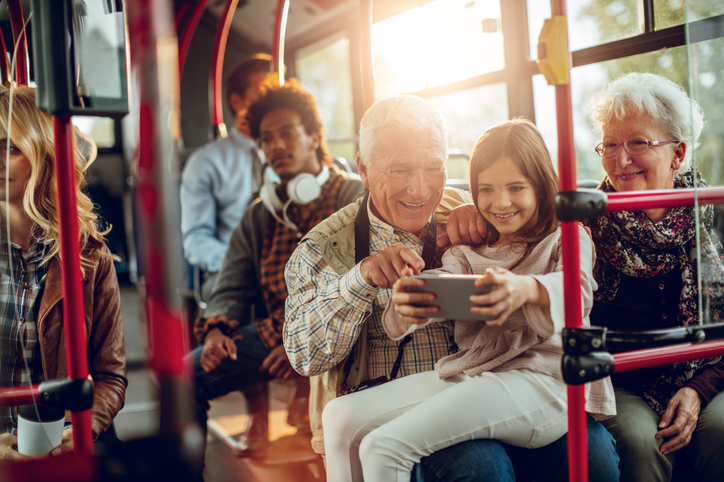 Grandparents look at a smartphone with their granddaughter whilst sat on a bus