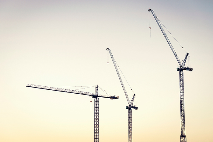Image of three cranes silhouetted against the sky.