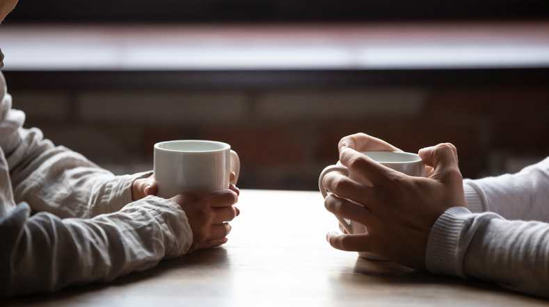 Two pairs of hands clasp coffee cups on a table