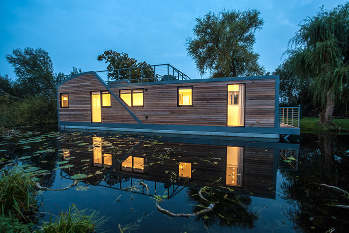 Photo of a luxury houseboat with wooden exterior on the water at dusk
