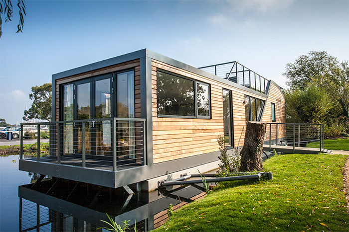 Photo of a luxury, modern houseboat with wooden exterior.