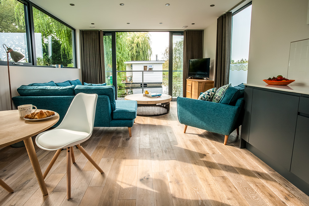 Photo of the living room on a luxury houseboat, with a view to the water and trees outside.