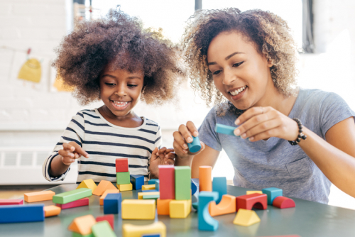 Mother and young daughter playing together with colourful bricks