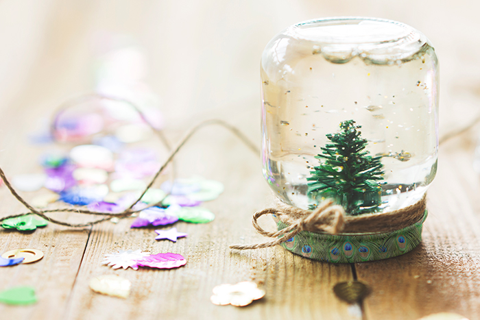 Close up of a small jar with a christmas tree in, along with some craft supplies.